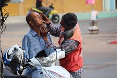 Selfless act. Motorbike taxi driver shaving armless man. Stock Images