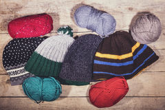 Selfmade balaclava, woolen caps and balls on wooden table. Handiwork Royalty Free Stock Images