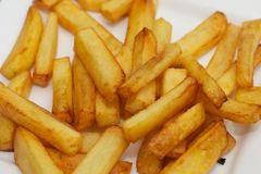 Selfmade fries. Plate with selfmade yellow and light brown fries Royalty Free Stock Photos