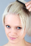 Selfmade Hairstyle. Blonde european woman styling her hair. Portrait with just the face and a hand holding a comb Royalty Free Stock Images