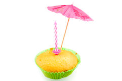 Selfmade muffin with umbrella and candle. Selfmade muffin with umbrella isolated on white background Royalty Free Stock Image