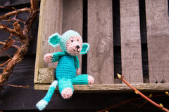 Selfmade stuffed monkey outdoor. Crocheted selfmade monkey toy sitting on crate outdoor Royalty Free Stock Images