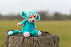 Selfmade stuffed monkey outdoor. Crocheted selfmade monkey toy sitting on fence outdoor Royalty Free Stock Photos