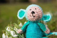 Selfmade stuffed monkey outdoor. Crocheted selfmade monkey toy sitting in flowers outdoor Stock Photo