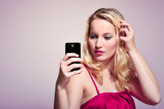Selfportrait in pink. Young woman looking at her smart phone in live view modus, posing for a selfie Stock Images