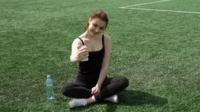 Selfshot on a stadium lawn. Attractive young is taking a selfie while sitting on a sport stadium lawn on smartphone camera stock video