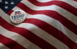 Trump-Pence 2020 campaign badge against United States flags. royalty free stock image