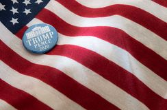 Trump-Pence 2020 campaign badge against United States flags. stock images