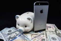 Selinsgrove, PA, los E.E.U.U. - 31 de marzo de 2019: Un iPhone de Apple se sienta encima de una pila de moneda de Estados Unidos fotografía de archivo