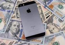 Selinsgrove, PA, USA - March 31, 2019 : An Apple iPhone sits on top of a pile of United States currency. royalty free stock photo