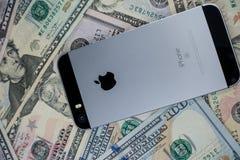Selinsgrove PA, USA - mars 31, 2019: En Apple iPhone sitter överst av en hög av Förenta staternavaluta fotografering för bildbyråer
