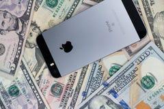 Selinsgrove PA, USA - mars 31, 2019: En Apple iPhone sitter överst av en hög av Förenta staternavaluta arkivfoton