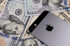 Selinsgrove PA, USA - mars 31, 2019: En Apple iPhone sitter överst av en hög av Förenta staternavaluta royaltyfri foto