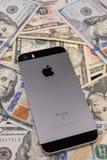 Selinsgrove PA, USA - mars 31, 2019: En Apple iPhone sitter överst av en hög av Förenta staternavaluta royaltyfria foton