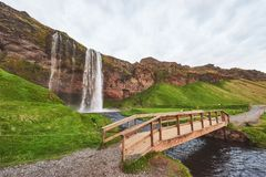 Seljalandfoss waterfall at sunset. Bridge over the river. Fantastic nature. Iceland. royalty free stock photography