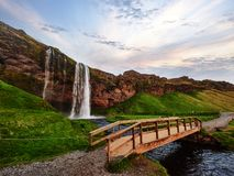 Seljalandfoss waterfall at sunset. Bridge over the river. Fantastic nature. Iceland stock photography