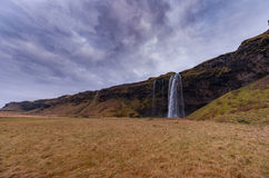 Seljalandsfoss Waterfall in Iceland. One of the ost Famous Waterfall in Iceland. Cloudy Sky. Royalty Free Stock Images