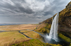 Seljalandsfoss Waterfall in Iceland. One of the ost Famous Waterfall in Iceland. Cloudy Sky. Wide Angle. Landscape. Stock Photography