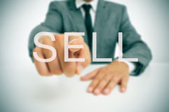 Sell. Businessman sitting in a desk pointing the word sell written in the foreground Stock Photography