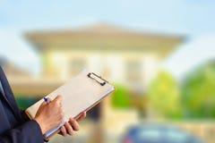 Sell för manaffärsrepresentant hus med datoren på oskarp bakgrund för hus och för träd royaltyfri bild