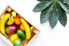 Sell friuts on the market. Bananas, oranges, mango in box on white background top view Stock Images