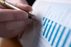 Sell Rates. Hand with a pen, inspecting bisiness diagramm royalty free stock photos