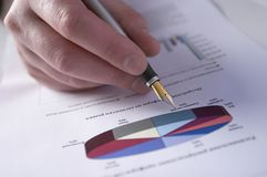 Sell Rates. Hand with a pen, inspecting bisiness diagramm royalty free stock images