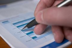 Sell Rates. Hand with a pen, inspecting bisiness diagramm stock photography