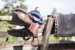 Sella del cavallo che appende su un recinto di legno Immagine Stock Libera da Diritti