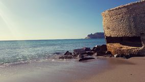 Sella del Diavolo promontory viewed by Poetto beach, Cagliari, Italy Royalty Free Stock Images
