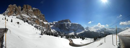 Sella Pass Panorama, Italy. 180 Degree sunny winter panorama of the road to Sella Pass in the Italian Alps near Val Gardena, Alto Adige, Italy. The Sella royalty free stock photography