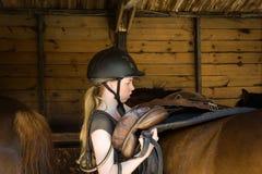 Selle de fille un cheval Photos stock
