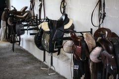 Selle di cuoio ed attrezzature del cavallo che riposano sui ganci in puntina r fotografie stock
