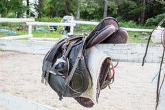 Selle noire utilisée d'équitation de dressage avec le périmètre, l'étrier et les gants d'équitation images libres de droits