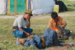 Selle traditionnelle de cheval de difficulté mongole d'hommes devant l'entrée nomade de tente de yurt vers Kharkhorin, Mongolie photos libres de droits