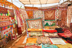 Seller of antique carpets shows colorful embroidered bedspreads at the marketplace of oriental bazaar Stock Photos
