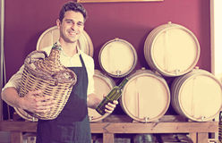 Seller in apron holding big wicker bottle with wine in store. Smiling man seller in apron holding big wicker bottle with wine in store Stock Photo