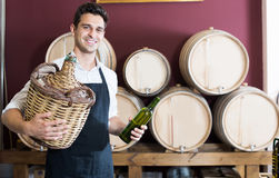 Seller in apron holding big wicker bottle with wine in store. Smiling man seller in apron holding big wicker bottle with wine in store Stock Images