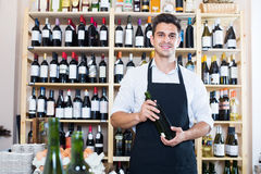 Seller in apron holding bottle of wine. Portrait of cheerful smiling male seller in apron holding bottle of wine and standing in alcohol section in store Stock Images
