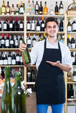 Seller in apron holding bottle of wine. Portrait of joyful male seller in apron holding bottle of wine and standing in alcohol section in store Royalty Free Stock Photos