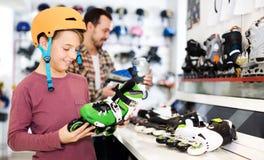Seller assisting boy in choosing roller-skates Stock Image