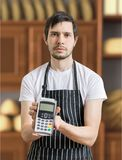 Seller in bakery is passing payment terminal for paying with credit card Royalty Free Stock Image