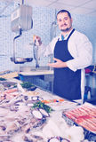 Seller behind scales and fish counter showing fish Royalty Free Stock Images