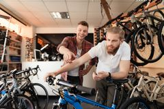 A seller at a bicycle store helps a young buyer choose a new mountain bike. A men with a beard and a client looks carefully at the goods. Around them there are royalty free stock image