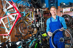 Seller with bike wheel in hand in store. Cheerful man seller wearing uniform fixing bike in bike store Royalty Free Stock Photos