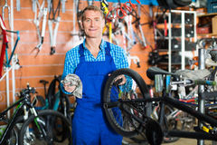 Seller with bike wheel in hand in store. Positive smiling man seller wearing uniform fixing bike wheel in store Stock Photos