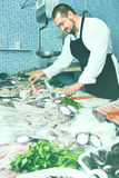Seller in black apron shows fish counter Stock Image