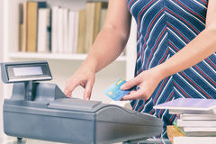 Seller at bookstore using cash register Royalty Free Stock Photography