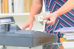 Seller at bookstore using cash register Stock Images