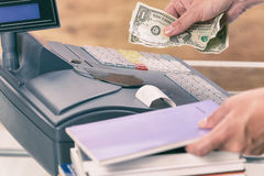 Seller at bookstore using cash register Royalty Free Stock Photo